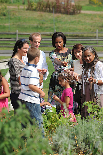 United States First Lady Michelle Obama and chef Dan Barber speak with children working in the herb garden as she tours Stone Barns Center Pocantico Hills, New York on Friday, September 24, 2010 with a large group of other First Ladies visiting New York for the United Nations General Assembly. They viewed the mobile chicken coop and herb garden while making a tour of the facilities.  A lunch was prepared with the food from the farm.  Also visible in the photo is Elisabeth Preval of Haiti at right..Credit: Andrea Renault / Pool via CNP