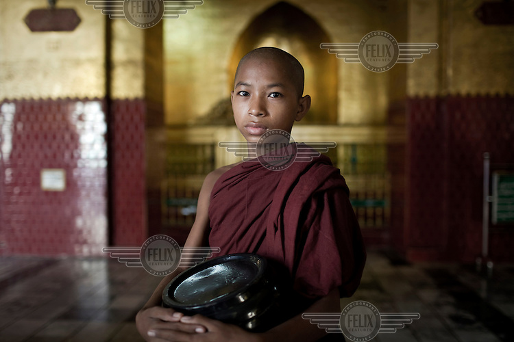 A young monk collects alms at a monastery on the outskirts of Mandaly where some 2,300 monks live and study.
