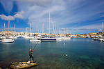 A man fishes in the Grand Harbour of Malta.