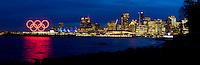Olympiastadt Vancouver 2010..Skyline von Vancouver mit den leuchtenden olympischen Ringen im Coal Harbour.  Ansicht vom Stanley Park..Die leuchtenden Segel vom Canada Place wechseln alle paar Sekunden die Farben.