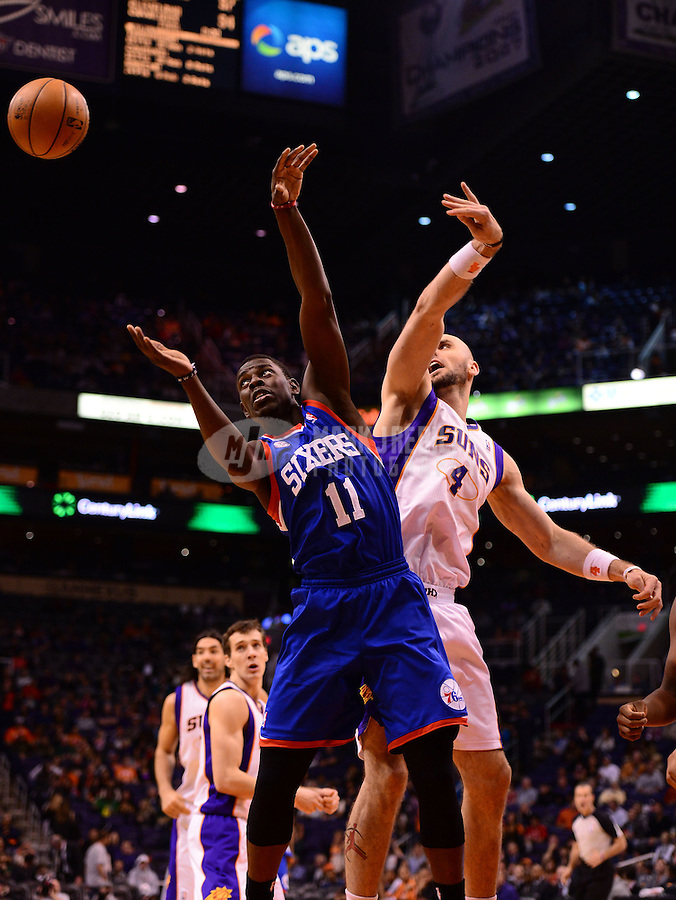 Jan. 2, 2013; Phoenix, AZ, USA: Philadelphia 76ers guard Jrue Holiday (11) and Phoenix Suns center Marcin Gortat (4) battle for a rebound in the second half at the US Airways Center. The Suns defeated the 76ers 95-89. Mandatory Credit: Mark J. Rebilas-USA TODAY Sports