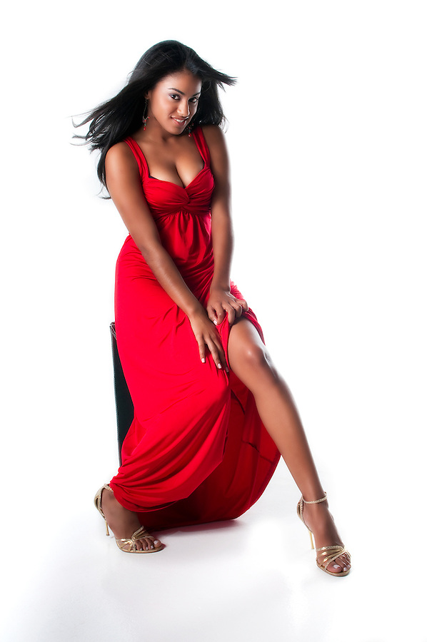 Latin glamour model with red dress in sensual posse.