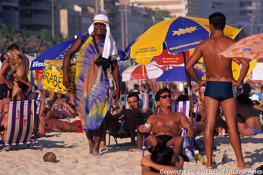 Rio de Janeiro lifestyle, young tanned people enjoy Ipanema beach, street vendor dressed with colorful clothes and turban selling arabic food at the beach sand. Rio de Janeiro, Brazil.