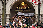 People watch from the Trump International Hotel as United States President Donald Trump and First Lady Melania Trump walk in their inaugural parade after being sworn-in as the 45th President in Washington, D.C. on January 20, 2017.     <br /> Credit: Kevin Dietsch / Pool via CNP