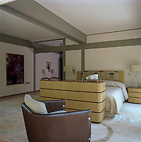 In this spacious bedroom the Deco-style cabinet at the end of the bed houses a hidden television