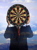 Dartboard Man - a businessman holding a dartboard in front of his face, Rocky Mountains in background.