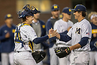 Michigan Wolverines catcher Casey Buckley (24) shakes hands with pitcher Keaton Carratini (28) after the NCAA baseball game against the Eastern Michigan Eagles on May 8, 2019 at Ray Fisher Stadium in Ann Arbor, Michigan. Michigan defeated Eastern Michigan 10-1. (Andrew Woolley/Four Seam Images)
