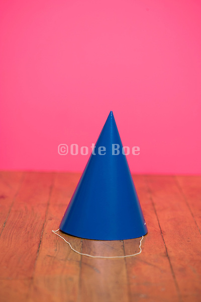 a blue paper party hat on a wooden floor against a pink wall