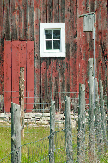 A birdhouse is attached to a fencepost with a nearny barn looking on, Door County, Wisconsin