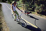 A young woman and her dog ride the bike path in the town of Jackson, Wyoming.