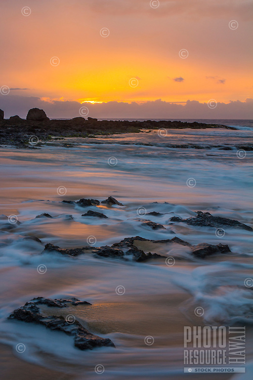 At sunset, a long exposure captures a soft look on the receding water at Ke Iki on the North Shore of O'ahu.