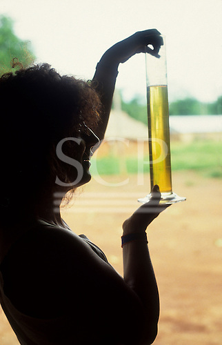 A-Ukre Village, Brazil. Anita Roddick looking at Brazil nut oil in a glass measuring cylinder; Xingu Reserve.