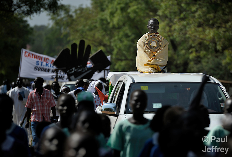 Perched on the back of a truck, a priest holds the Blessed Sacrament as Catholics participate in a procession through the streets of Juba on November 20 to pray for a peaceful January 2011 referendum on Southern Sudan's secession from the north of the country. The independence vote has widespread support throughout Southern Sudan, including among Catholics and other Christians. The Blessed Sacrament was carried on the back of a truck throughout the entire procession. NOTE: In July 2011 Southern Sudan became the independent country of South Sudan.