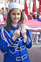 Young girl an boys walking along the parade and carrying the country flag and Ataturk pictures and singing the national anthem during the celebration of Turkey's national day at Istiklal Street, Taksim.