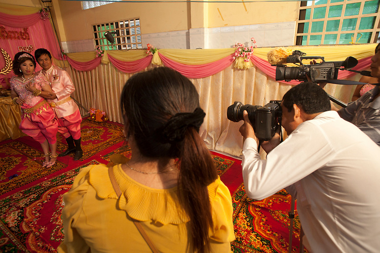 A couple poses for formal photos at a buddhist wedding in a small village outside of Phnom Penh, Cambodia. <br /> <br /> Photos &copy; Dennis Drenner 2013.