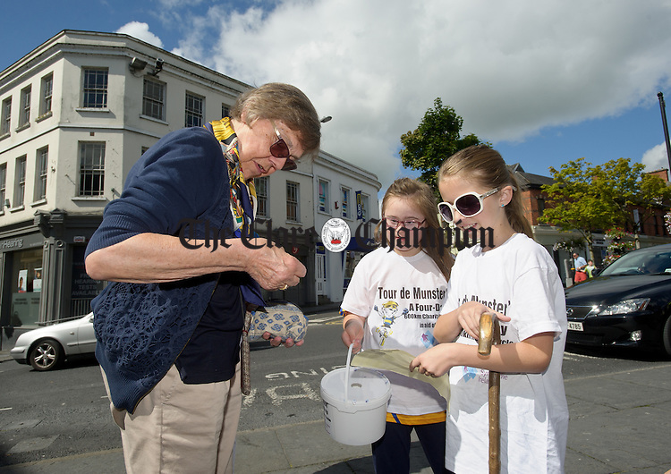 A passer by donates money to collectors Megan O Brien, Quin and Ava O Regan, Kilmurry, during the arrival in Ennis of the Tour de Munster, a four day 600km charity cycle in aid of Down Syndrome Ireland. photograph by John Kelly.
