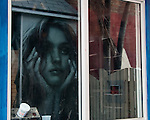 A beauty product poster across the alley is reflected in a window.  Key West, Florida, USA.