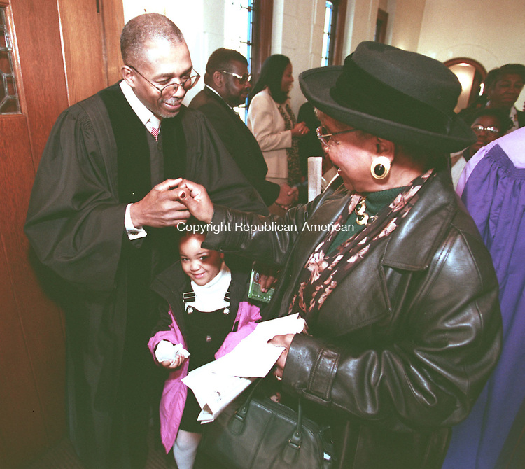 WATERBURY, CT 11/22/98--1122DC02.tif .Rev. Larry Green (L) greets Ammie Piland (R) as seven year old Cheyenne Barboca tries to cut thru after Sunday services at the Grace Babtist Church. -DOUG COLLIER staff photo (Filed in Scans/Scan-In)