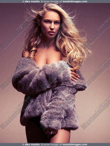 Glamour portrait of a beautiful young woman wearing a fur coat over naked body
