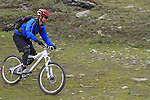 Mountain biker ascends via the Gornergrat train and descends past the Matterhorn, above Zermatt, Switzerland.