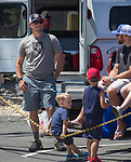 Brien Carlin with four-year-old Remy and four-yesr-old Troy watch the annual Reno Rodeo Cattle Drive come into Reno, Nevada on Thursday, June 14, 2018.