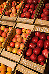 Crates of apples and peaches at a road side stand