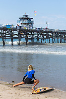 Female Surfer stretching on the Beach at San Clemente Pier