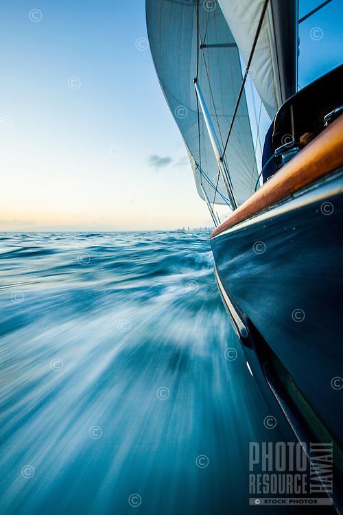 Waves streak past a luxury yacht at sunset off the coast of Waikiki, O'ahu.