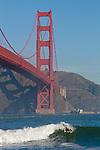 A masked man surfs under the Golden Gate Bridge and Marin Headlands in San Francisco, CA.