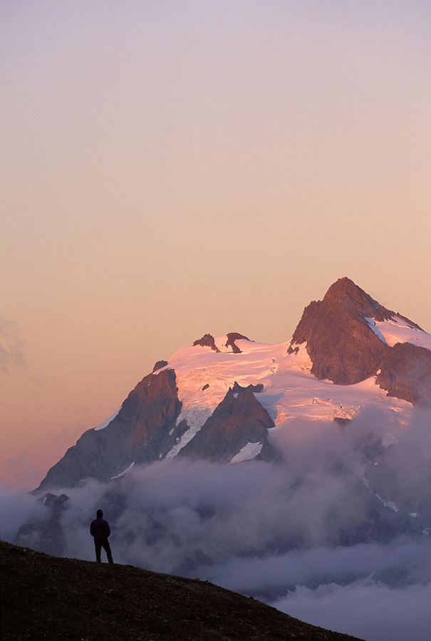 Hiker standing on ridge below Mt Shuksan at sunset, North Cascades, Cascade Mountains, Washington