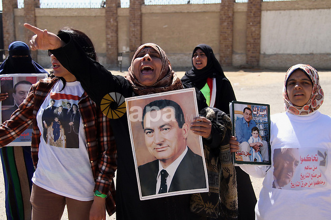 Supporters of former Egyptian president Hosni Mubarak hold his poster outside the police academy in Cairo, Egypt, on Feb. 19, 2014. Photo by Mohammed Bendari