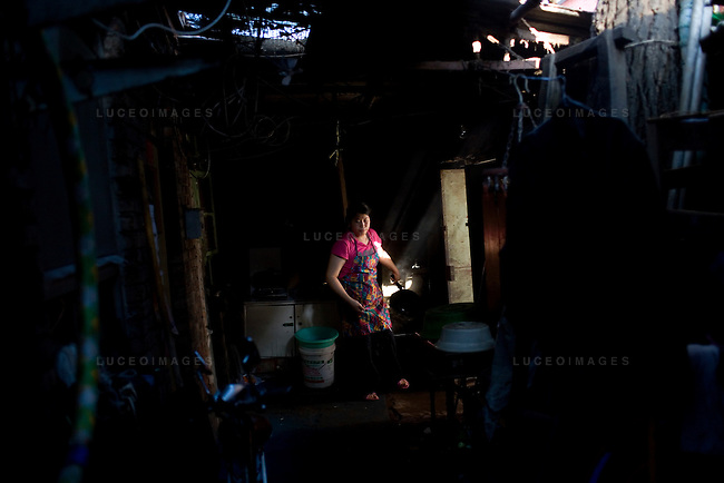 Liu Guo Min washes her frying pan in a community kitchen that is missing large portions of the roof in a hutong in Beijing, China on Friday, August 22, 2008.  Kevin German