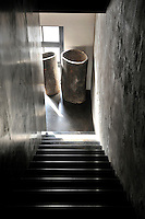 A view from the top of a staircase with rough, exposed stone side walls. Two hollowed-out tree trunks stand at the bottom.