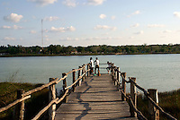 Boys fishing from a pier on Lake Coba in background, Coba, Quintana Roo, Mexico.
