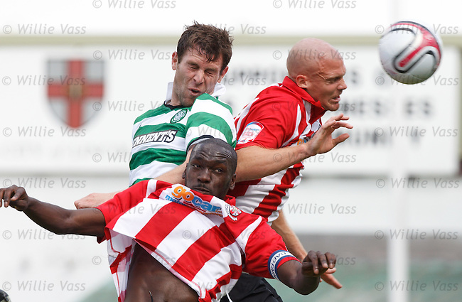 Celtic new signing Daryl Murphy directs a header towards goal as the Lincoln City defenders charge into him