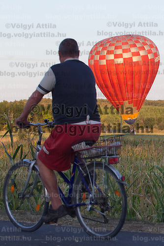 A biker watches a balloon landing during the Velence Lake International Hot Air Balloon Festival in Agard, Slovakia on September 10, 2011. ATTILA VOLGYI