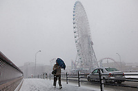 A man carrying an umbreallla struggles in a blizzard near the Cosmo Clock big wheel in Minato Mirai, Sakuraguicho, Yokohama, Kanagawa, Japan. Friday February 14th 2014