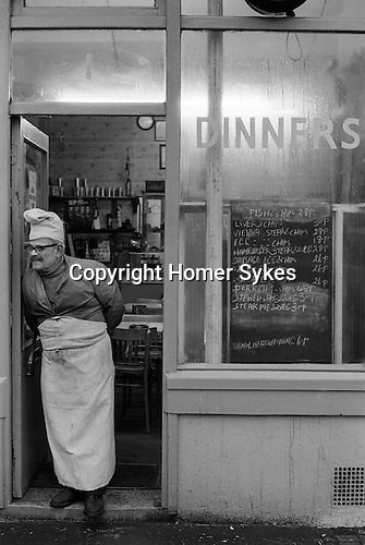 Whitechapel, London. 1974<br /> The proprietor in chefs hat and apron, buttoned up to his jacket, stands outside his greasy spoon Dinners caf&eacute; in Brick Lane waiting for lunchtime customers. The blackboard dinner menu is almost everything with chips. Fish &amp; chips 27p, Liver &amp; chips 30p, Vienna steak &amp; chips 28p, Egg &amp; chips 18p, Hamburger steak &amp; 2 veg 28p, Sausage egg &amp; chips 26p, <br /> 2 egg &amp; chips 26p, 2 sausage &amp; chips 26p, Pork chop &amp; chips 45p, Stewed lamb &amp; 2 veg 30p, Steak pie &amp; 2 veg 30p, and finally for dessert Semolina pudding  will cost you 6p. The Vienna steak &amp; chips, perhaps gives a clue to his nationality.