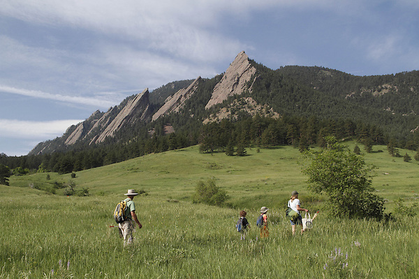 Family hiking at the base of the Flatirons rock formation in Chautauqua Park, Boulder, Colorado, USA .  John leads private photo tours in Boulder and throughout Colorado. Year-round.