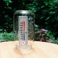 MEASURING THE GREENHOUSE EFFECT (1 of 2)<br /> Jar and Thermometer<br /> After an outdoor thermometer has been in the sun for 15 minutes, it is placed inside a large jar for 15 minutes.  Comparing the two different  temperatures shows a rise in the temperature in the jar which acts as the greenhouse.