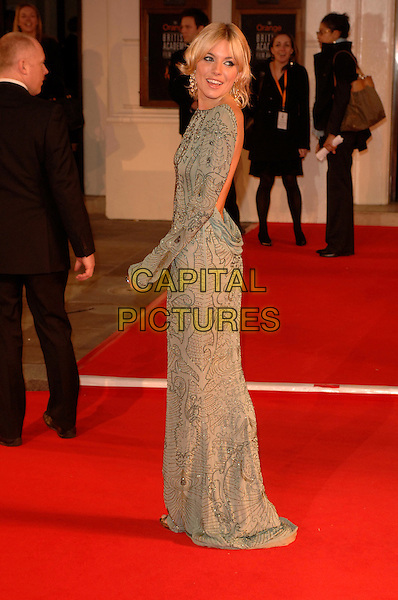 SIENNA  MILLER.Red Carpet Arrivals at The Orange British Academy Film Awards (BAFTA's) held at the Royal Opera House, Covent Garden, London, England, February 11th 2007..full length grey silver gold beaded patterned long sleeved dress looking over shoulder backless low back behind.CAP/DH.©David Hitchens/Capital Pictures.