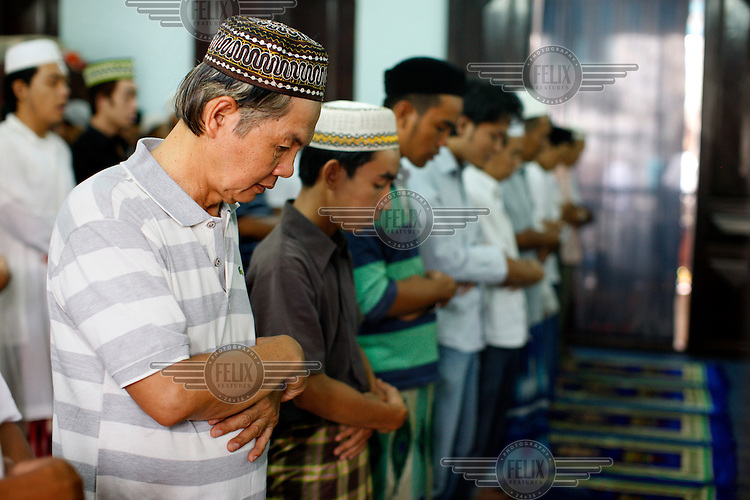 Men say Friday prayers in a Mosque.