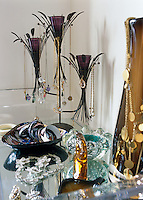 Necklaces and trinkets hang from a contemporary candelabra with bracelets and rings kept in dishes on this dressing table