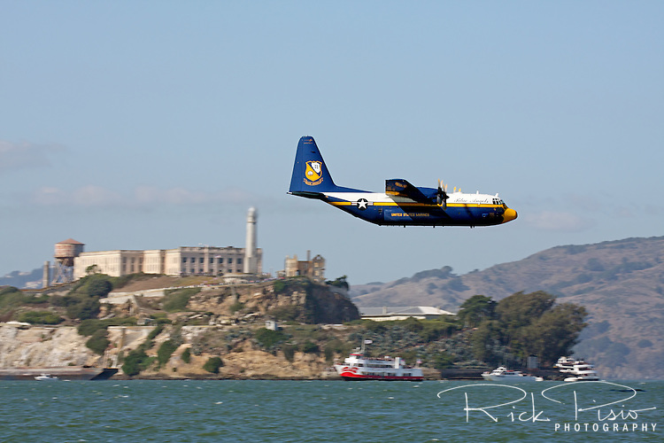 The C-130 Hercules affectionately know as Fat Albert makes a pass along the waterfront between San Francisco and Alcatraz. Serving as the support aircraft for the U.S. Navy Blue Angels the Marine crewed aircraft often preceeds the Navy's flight demonstration at air shows around the world as well as serving as the team's support aircraft.