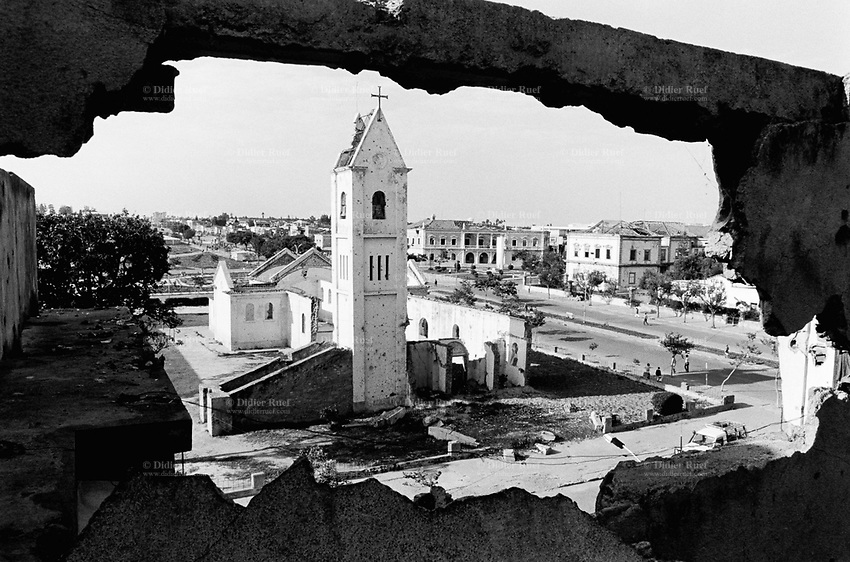 Angola. Province of Bié. Kuito. The town was heavily destroyed in 1993-1994 and 1998-1999 due to the intense civil war between the Government and Unita. Bullet and gun holes on the wall. View on the town center and the catholic church. © 2000 Didier Ruef