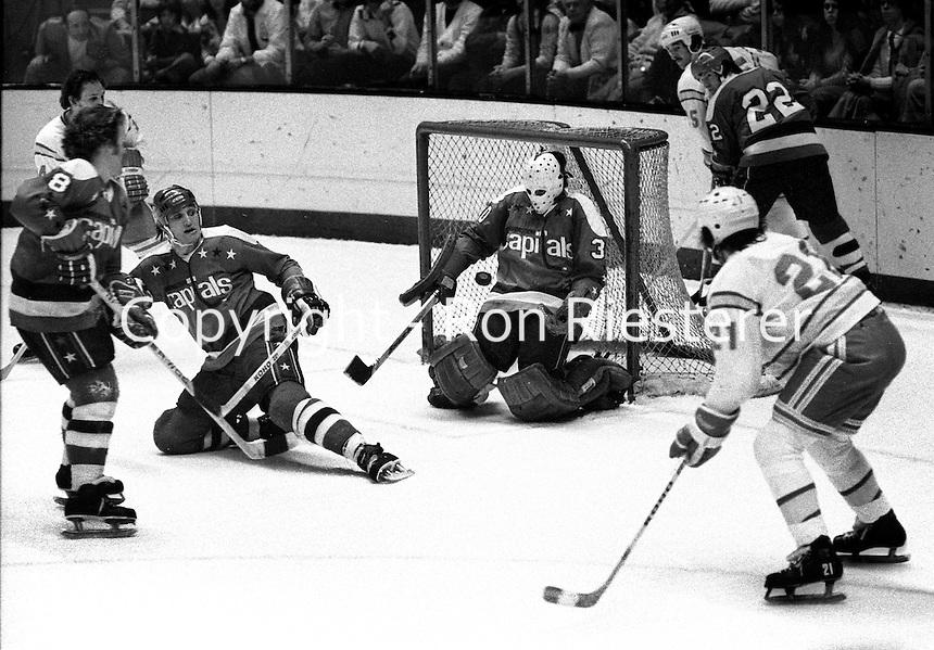 California Golden Seals vs Washington Capitols. goalie Bernie Wolfe blocks shot, from Dennis Maruk, Jack Lynch and Don McLean. (1975 photo/Ron Riesterer)
