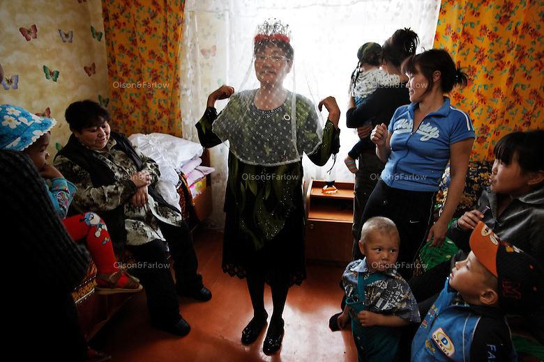Older woman is fake bride in the home the morning of the wedding.  Tamara Nutaime dons a veil.