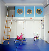 In a child's bedroom the platform bed is situated on a mezzanine with three brass porthole windows, reached by a ladder from the bright blue rubber flooring below