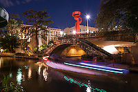 "Another capture of San Antonio Torch of Friendship which stands tall along the river walk from the road above in this cityscape image after dark. This Torch of Freedom sculpture was created and erected in 2002 by a world famous scupture Sebastián. La Antorcha de la Amistad which is ""Spanish for ""The Torch of Friendship"". The Torch of Freedom is a unique abstract sculpture art work which stand at 65 feet high along the riverwalk and at night it can be seen from the San Antonio riverwalk below like a beacon.  We like this angle as the riverboats criss crossed under the bridge they left this colorful trail of light on top of the water from the long exposure from the river walk below. The San Antonio river walk is probaby the biggest attraction for the city, for tourist and locals alike, on any given day but especially on weekends night the crowds swell sometimes making it almost impossible to walk, but the festive mood will keep you coming back."