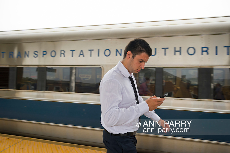 During evening rush hour, a young man in business shirt and tie leaves the train and checks his smart phone as he walks on elevated platform of Merrick train station of Babylon branch, after MTA Metropolitan Transit Authority and Long Island Rail Road union talks deadlock, with potential LIRR strike looming just days ahead.